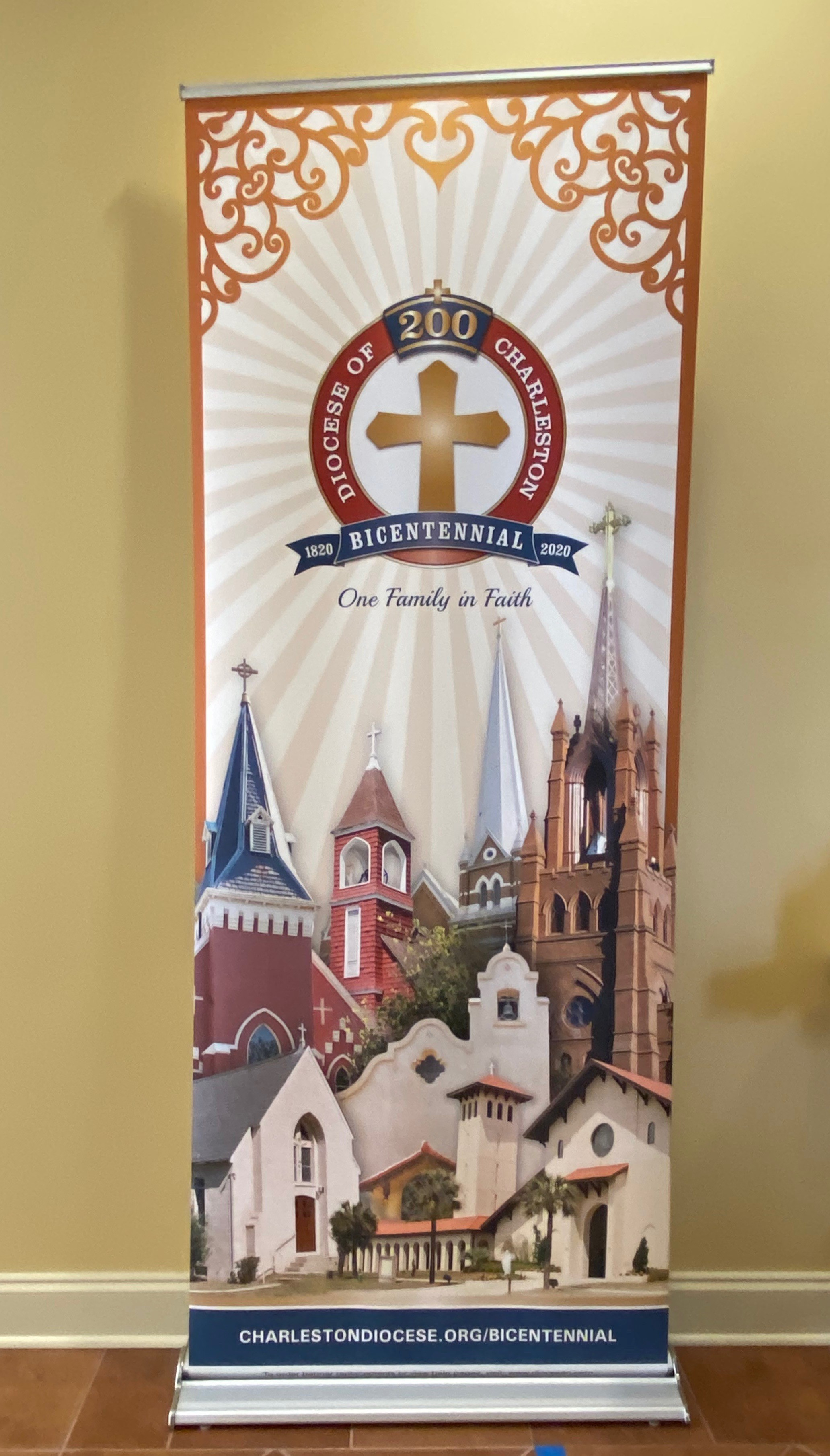 bicentennial banner with churches and a gold cross in a red boarder